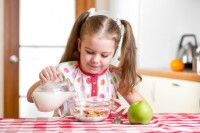 kid girl preparing corn flakes with milk