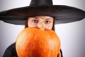 Young witch holding a pumpkin (focus on pumpkin)