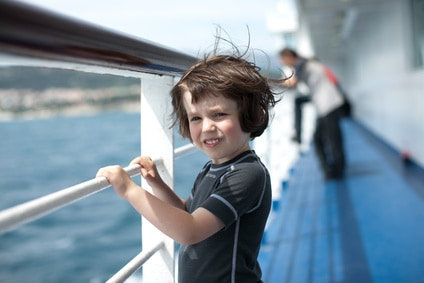 a happy child on ferry boat looking out to sea