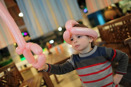 Child playing with balloon sword and helmet