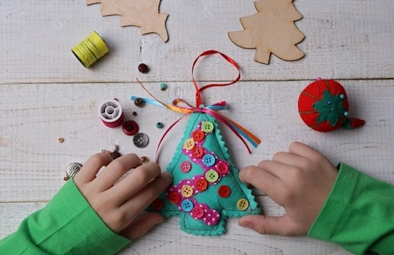 Child making felt Christmas Tree decoration ornament close up . Kids Art, Art Projects, Handmade New Year decorations .Happy family concept