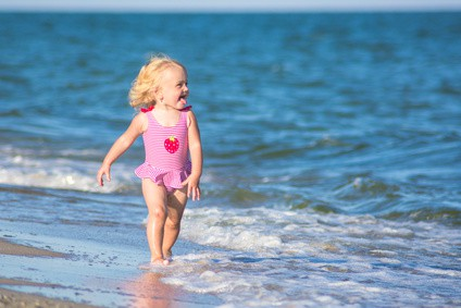 Smiling girl walks by the water