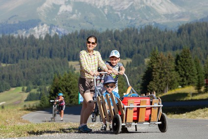 The happy woman and two boys walk with luggage to mountain hotel in Alps