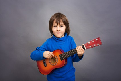Preschool child, playing little guitar, isolated image